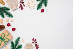 Christmas background with present in craft paper, glass and wooden decorations, pine cones, berries, fir tree branches. Flay lay top view, copy space