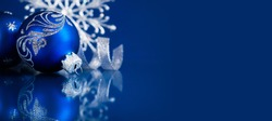 Christmas background with silver and blue ornaments on dark blue. Merry christmas greeting card, banner. Winter holiday xmas theme. Happy New Year. Space for text