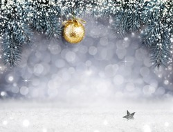 Christmas background with snow and golden ball on spruce branch.