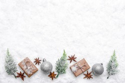 Christmas background with snow, layout with christmas gifts, fir trees and ornaments, new year composition, top view, copy space