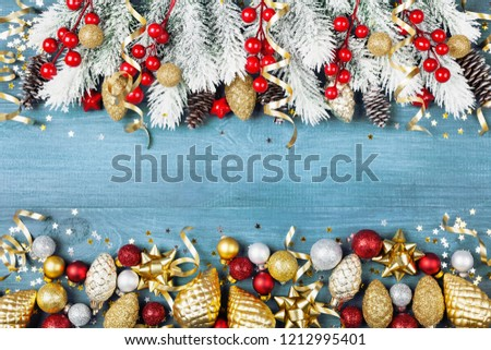 Christmas background with snowy fir tree and shiny holiday decorations on blue wooden table top view. Greeting card with space for text. #1212995401