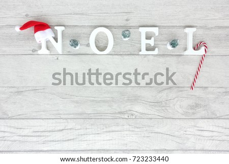 Christmas background with the words noel formed out of white wooden capital letters on grey wood background. #723233440
