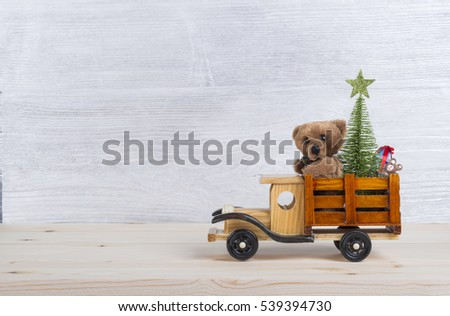 Stock Photo Christmas background with toys-wooden truck carries a teddy bear, Christmas tree, decorations and gifts. Silver and white wood background as a backdrop