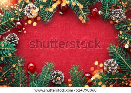 Christmas background with xmas tree, red ornaments and glowing golden bokeh lights on red canvas background. Merry christmas card. Winter holiday theme. Space for text. Happy New Year. #524990860