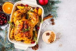 Christmas baked chicken with spices, orange and herbs, white background. Christmas food concept.