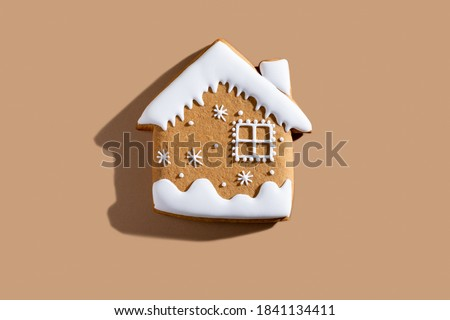 Photo of  Christmas bakery. Festive traditional cookies. Homemade culinary. Gingerbread biscuit figure house with white icing ornament isolated on beige pastel background.
