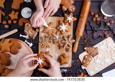 Christmas bakery. Friends decorating freshly baked gingerbread cookies with icing and confectionery mastic, view from above. Festive food, family culinary, Christmas and New Year traditions concept #747353830