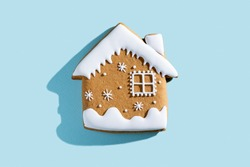 Christmas bakery illustration. Festive traditional cookies. Homemade culinary. Gingerbread biscuit figure house with white icing isolated on blue pastel.