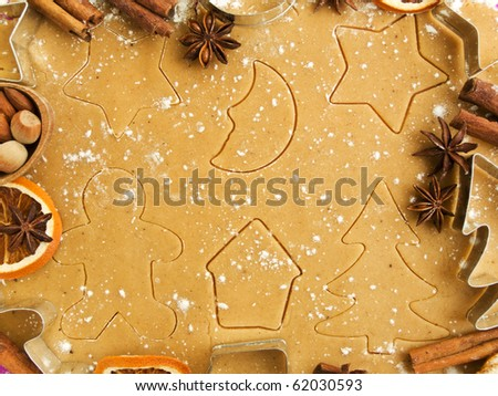 Christmas baking background: dough, cookie cutters, spices and nuts. Viewed from above.