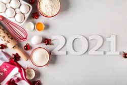 Christmas Baking Background 2021. Food Ingredients for cooking New Year baking.Eggs, flour,sugar recipe for pastry. Festive decorations.Copy space Top view.
