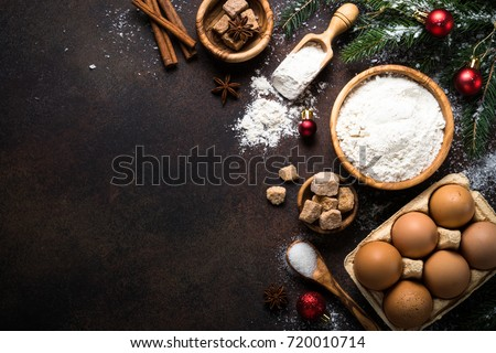 Christmas Baking background. Ingredients for cooking christmas baking on dark stone or metal background. Top view with copy space.