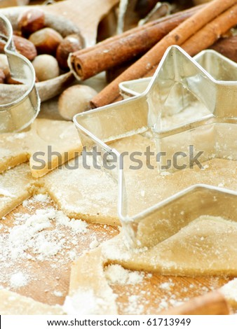 Christmas baking background with dough, cookie cutters and spices. Shallow dof.