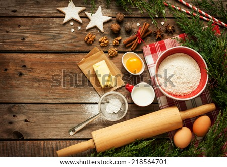 Christmas - baking cake background. Dough ingredients and decorations on vintage planked wood table from above. Rural kitchen layout with free text space.