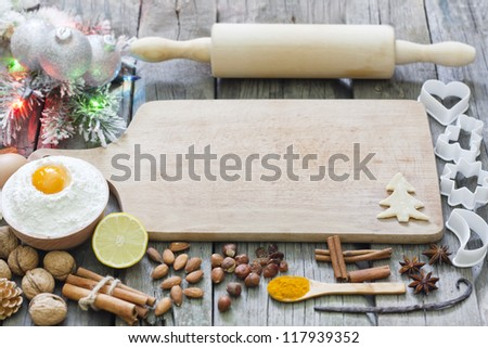 Christmas baking cookies with baubles  spices and empty cutting board abstract background