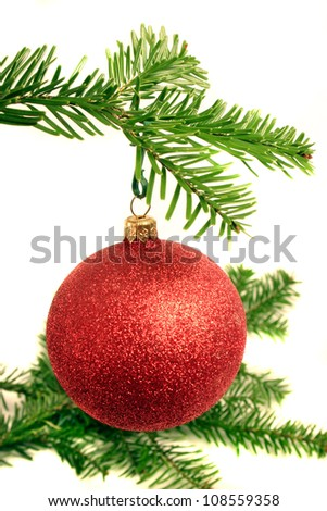Christmas ball and fir branch over white background.