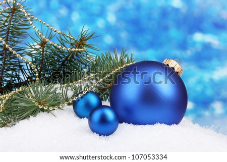 Christmas ball and green tree in the snow on blue