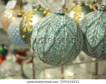 Christmas ball mint color closeup. Behind him, a blurred background of balls stretching into the distance. Concept of Christmas and new year decorations and decorations