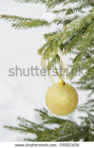 Christmas ball on the natural fir tree with snow.