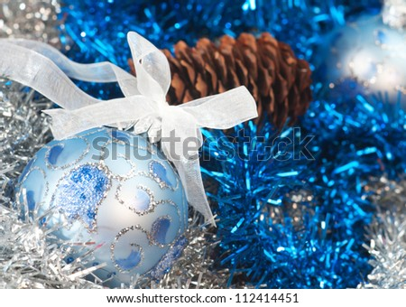 Christmas ball on the tinsel background