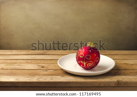 Christmas ball on white plate on wooden table