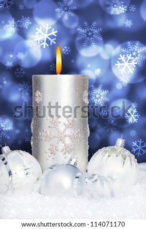 christmas ball ornament and candle in snow before blue bokeh background