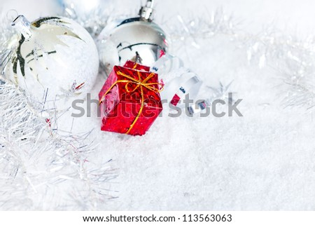christmas ball ornament and little gift in snow