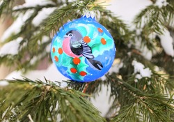 Christmas ball with a picture of a bird on a real Christmas tree with snow. Blue Christmas ball with bullfinch with red breast. Glass ball handmade