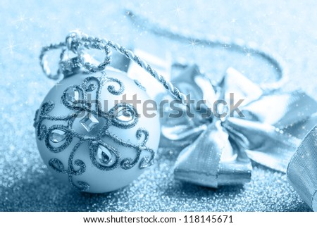 Christmas ball with ribbon in blue tone with glittering background