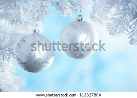 Christmas ball with snow branch hanging on blue background