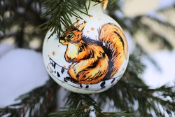 Christmas ball with the image of a squirrel on a real Christmas tree with snow. Glass ball handmade