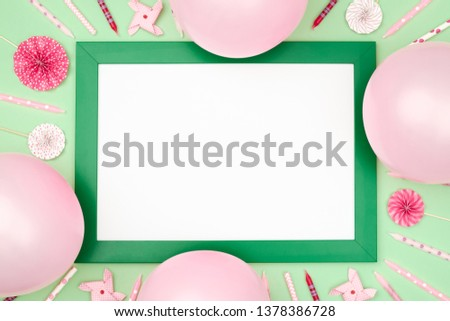 Christmas balls and picture frame on stylish colorful table top view. Fashion background. Flat lay. Party mockup or invitation