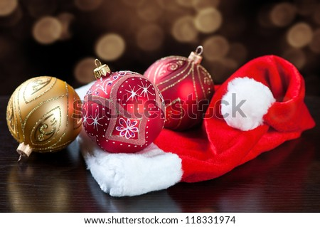 Christmas balls and Santa cap over defocused glittering lights background