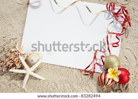 Christmas balls and seashells with blank card on the beach.