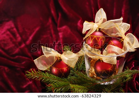 christmas balls in glass vase on burgundy velvet background