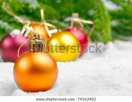 Christmas balls in the snow under the pine