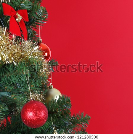 Christmas balls on Christmas tree branch, over red background