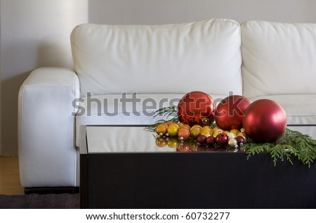 christmas balls on coffee table by white sofa in modern living room
