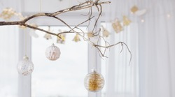 Christmas balls on golden branch on background window