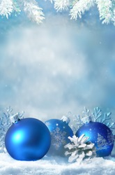 Christmas balls, snowflake pine branch on blue winter background.