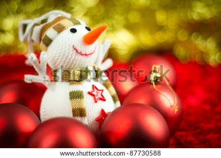 Christmas balls surrounding a wool snowman. Shallow Depth of Field.