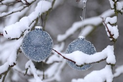 Christmas balls with beads  on snowy branches in the winter garden background.Christmas and New Year winter festive background.IPhone Wallpaper. Winter festive decor street