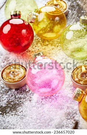 Christmas balls with golden candles on wooden background