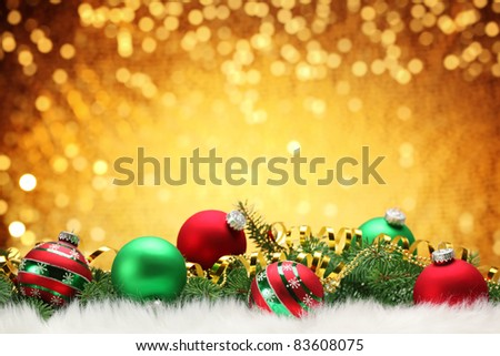 Christmas balls with pine branch on festive background.