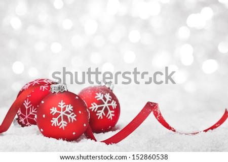 Christmas balls with ribbon on snow