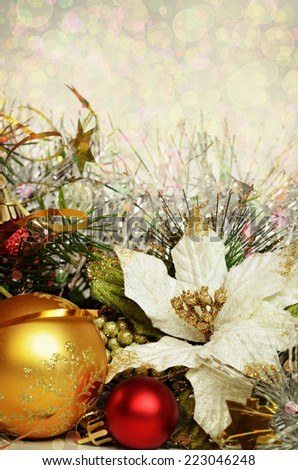 Christmas balls with tinsel and artificial poinsettia on a holiday background