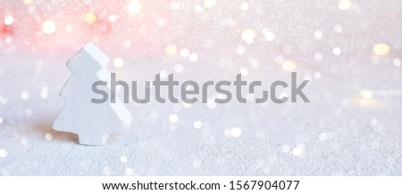 Christmas banner - small white wooden tree on abstract christmas lights background. Greeting card template christmas and New Year with copyspace for text.