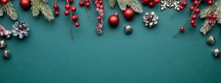 Christmas banner with classic decorations. Fir branches, red balls, jingle bells on turquoise background.