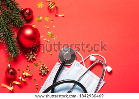 Christmas banner with festive decorations, medical stethoscope and facial masks on red background. Christmas greeting card for medics concept. Copy space for your text.