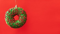 Christmas Banner with green donut in the form of a New Year toy on a red background. Celebration, food art, holiday concept.