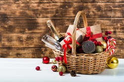 Christmas basket with champagne bottle and glasses, gifts with red satin ribbon, candy canes, pine cones, golden garlands on dark brown wooden background